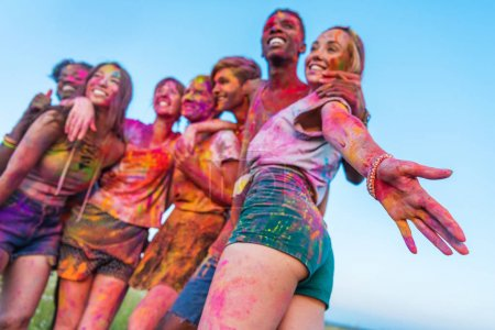 Photo for Low angle view of happy young friends with colorful paint on clothes standing together at holi festival - Royalty Free Image