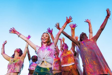 Photo for Happy young friends with outstretched hands having fun together at holi festival - Royalty Free Image