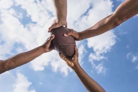 Hands holding american football ball