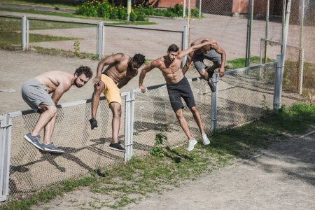 handsome men jumping over fence