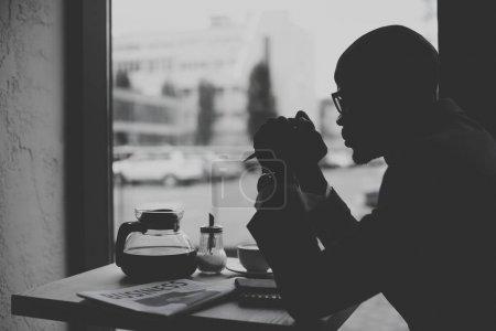 Photo pour Silhouette d'homme d'affaires afro-américain travaillant pendant la pause café dans un café, noir et blanc - image libre de droit