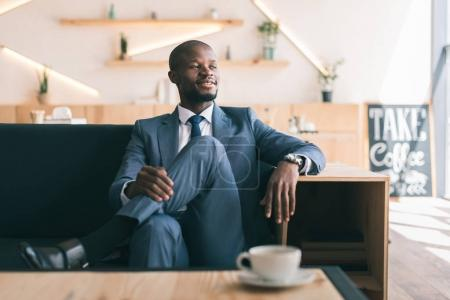 Photo for Smiling african american businessman sitting with cup of coffee in cafe - Royalty Free Image