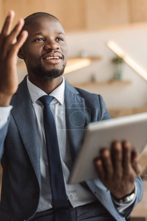 Photo for Handsome african american businessman having idea while working with digital tablet - Royalty Free Image