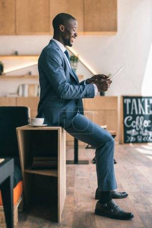 Photo pour Heureux homme afro-américain beau à l'aide de tablette numérique au cours de la pause café au café - image libre de droit