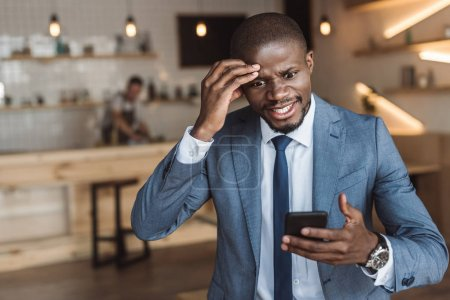 angry businessman using smartphone