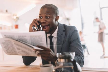 Businessman with smartphone reading newspaper