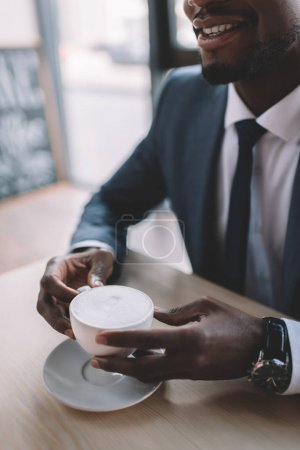 Photo for Cropped view of african american businessman holding coffee cup in cafe - Royalty Free Image