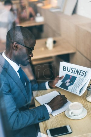 Photo for Serious handsome african american businessman with newspaper working in coffee shop - Royalty Free Image