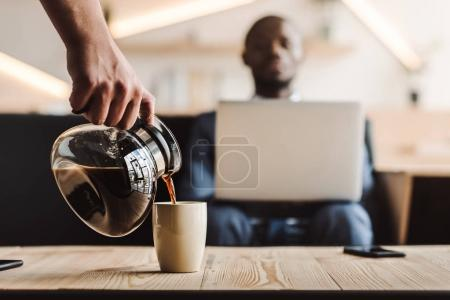 waiter pouring coffee into cup
