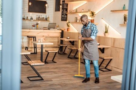 man brooming in coffee shop