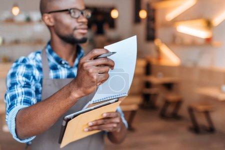 Photo pour Beau garçon afro-américain prenant la commande avec le bloc-notes et tablette numérique en café, mise au point sélective - image libre de droit