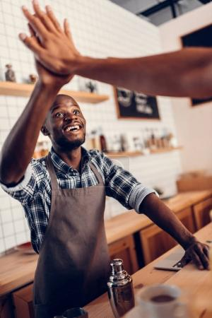 barista giving highfive to client