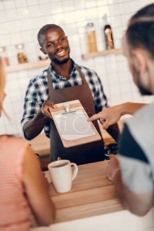 barista giving menu to clients