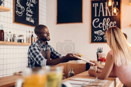 Photo for Handsome cheerful african american barista giving menu to clients on bar counter in cafe - Royalty Free Image