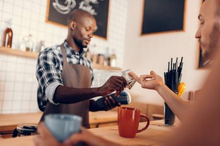Photo for Handsome african american barista taking cash payment on bar counter in cafe - Royalty Free Image