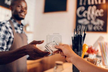 Photo pour Beau sourire afro-américaine barista prenant soulte comptoir au café - image libre de droit