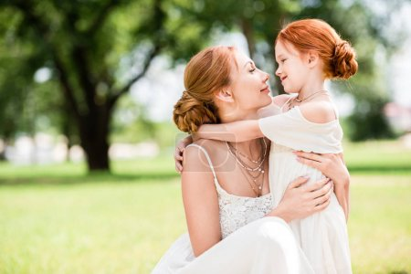 Photo for Happy redhead mother and daughter hugging and smiling each other at park - Royalty Free Image