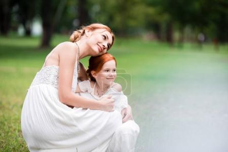 mother and daughter hugging at park