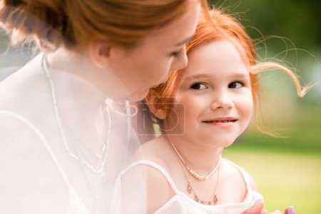 Photo for Portrait of beautiful happy red haired mother and daughter hugging at park - Royalty Free Image