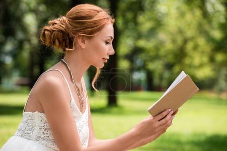 Photo pour Portrait de profil de livre de lecture de belle jeune femme blonde au parc - image libre de droit