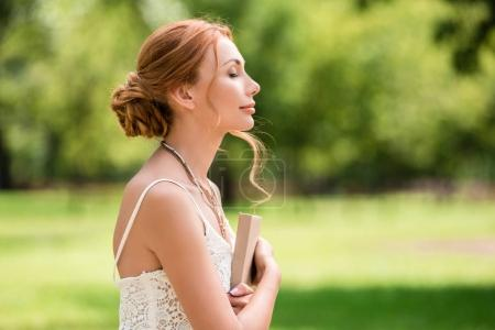 Photo for Side view of beautiful young woman with closed eyes holding book at park - Royalty Free Image