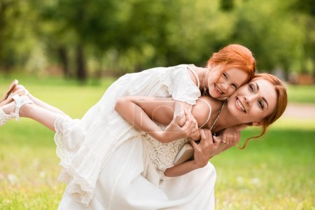 Photo for Happy young woman piggybacking adorable little daughter at park - Royalty Free Image