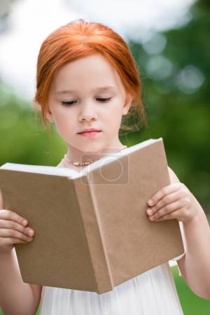 Photo for Cute pensive red haired girl reading book with blank cover at park - Royalty Free Image