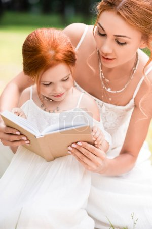 mother and daughter with book at park