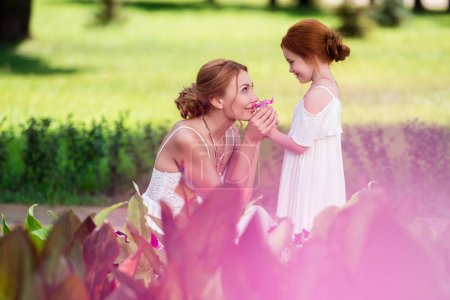 Photo for Side view of beautiful happy mother and daughter in white dresses smelling flowers near flower bed - Royalty Free Image