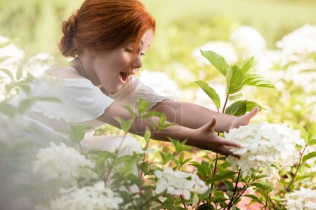 Photo for Cheerful redhead girl touching beautiful blooming flowers in park - Royalty Free Image