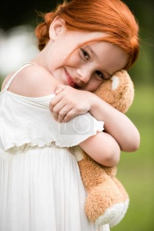 Photo for Adorable red haired girl hugging teddy bear and smiling at camera - Royalty Free Image