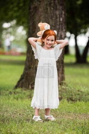 Photo for Cute little red haired girl in white dress holding teddy bear at park - Royalty Free Image