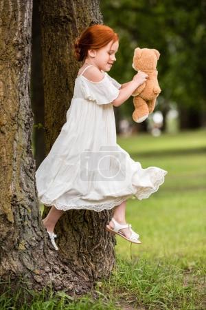 Girl with teddy bear in park