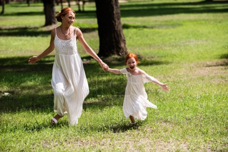 Photo for Beautiful happy mother and daughter holding hands while running together in park - Royalty Free Image