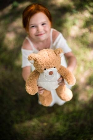 girl with teddy bear in park