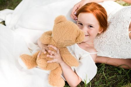 Mother and daughter with teddy bear in park