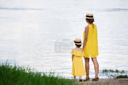 mother and daughter walking at riverside