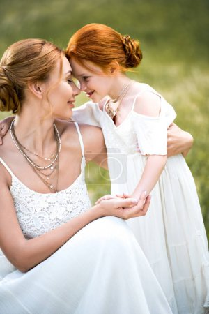 Photo for Beautiful happy mother and daughter in white dresses touching foreheads in park - Royalty Free Image