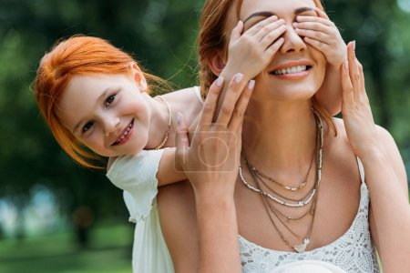 Photo for Adorable smiling redhead girl closing eyes of happy mother in park - Royalty Free Image