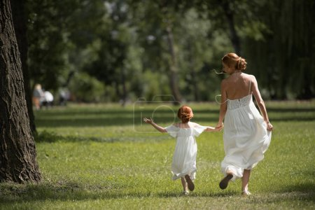 Photo for Back view of beautiful mother and daughter in white dresses holding hands and walking in park - Royalty Free Image