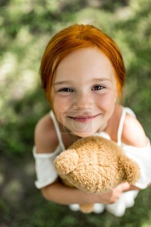 Photo for Close-up portrait of adorable red haired girl hugging teddy bear and smiling at camera - Royalty Free Image
