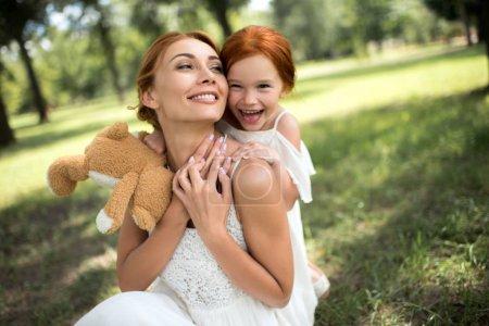 Photo pour Belle mère heureuse et fille avec ours en peluche étreignant ensemble dans le parc - image libre de droit