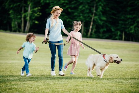 mother with kids and dog in park