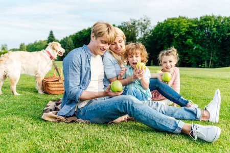 family eating apples at picnic