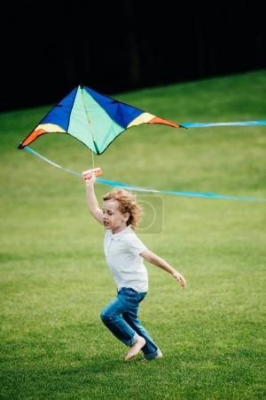 Boy playing with kite at park