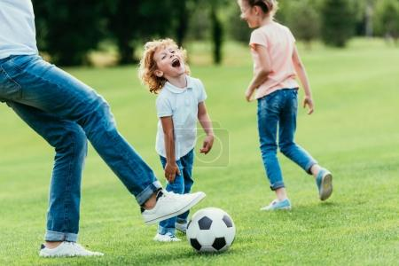 Photo for Cropped shot of father with happy kids playing soccer in park - Royalty Free Image