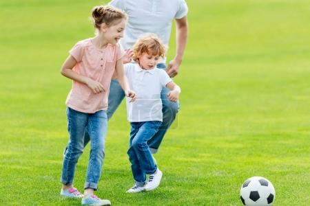 Father with kids playing soccer