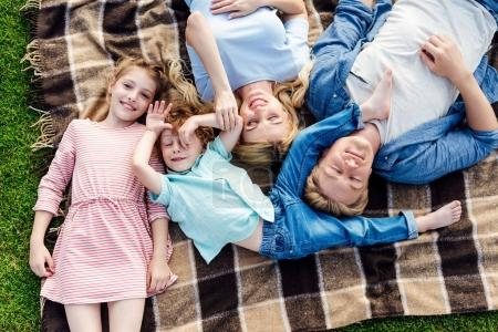 Happy family lying on plaid