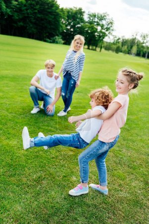 Photo for Happy parents looking at cute little children having fun together in park - Royalty Free Image