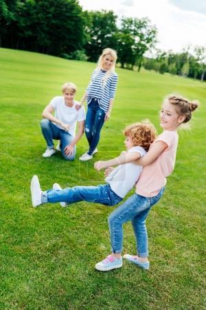 Photo pour Heureux parents regardant mignons petits enfants s'amuser ensemble dans le parc - image libre de droit